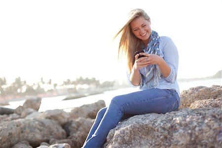 Young Woman Sitting on Rocks and Texting on Cell Phone at Beach, Jupiter, Palm Beach County, Florida, USA Stock Photo - Premium Royalty-Free, Code: 600-06732633