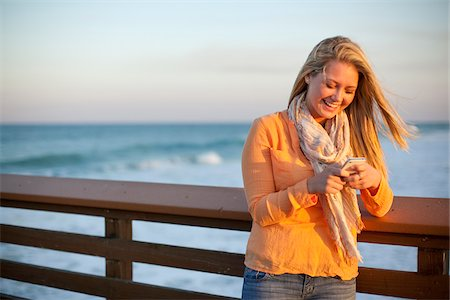 Young Woman Standing on Pier at Beach, Texting on Cell Phone, Jupiter, Palm Beach County, Florida, USA Stock Photo - Premium Royalty-Free, Code: 600-06732641