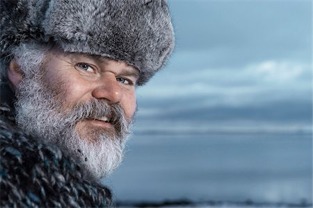 Man with gray beard wearing gray fur hat outdoors at winter in Iceland. Stock Photo - Premium Royalty-Free, Code: 600-06732713