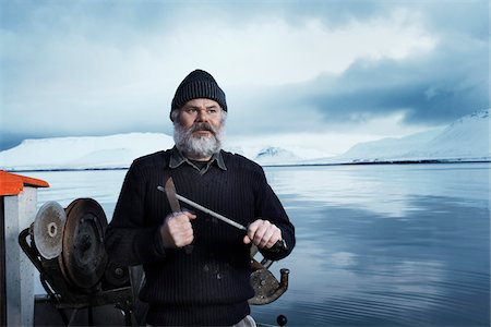 Fisherman with gray beard, standing on small boat, sharpening a knife on a winter day, Iceland. Stock Photo - Premium Royalty-Free, Code: 600-06732726