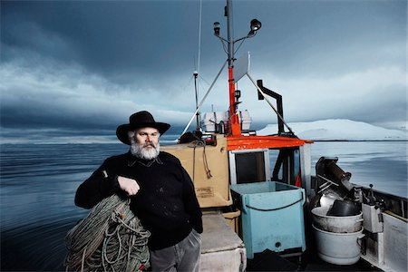 portrait looking away - Fisherman with gray beard on his boat on a winter day, Iceland Stock Photo - Premium Royalty-Free, Code: 600-06732723