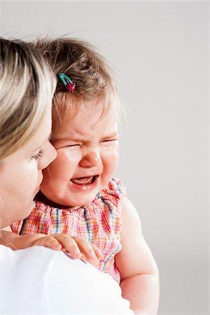 Portrait of Mother holding Crying Baby Girl, Studio Shot Stock Photo - Premium Royalty-Free, Code: 600-06752384