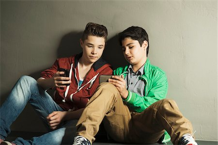 Teenagers looking at Cell Phones, Studio shot Stock Photo - Premium Royalty-Free, Code: 600-06752466