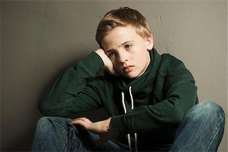 sad child sitting - Portrait of Boy Leaning on Hand, Studio Shot Stock Photo - Premium Royalty-Free, Code: 600-06752472