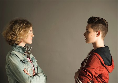 Teenage Boy and Girl Staring at Each Other with Arms Crossed, Studio Shot Stock Photo - Premium Royalty-Free, Code: 600-06752488