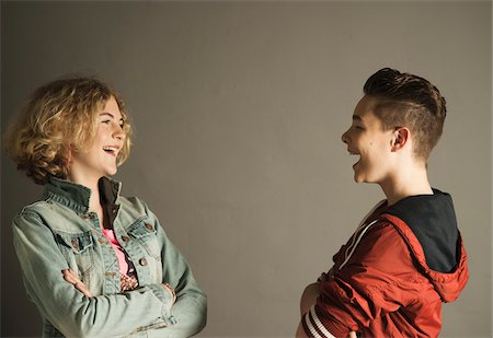 Teenage Boy and Girl looking at Each Other and Laughing, Studio Shot Stock Photo - Premium Royalty-Free, Code: 600-06752489