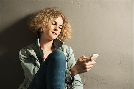 Teenage Girl using Cell Phone, Studio Shot Stock Photo - Premium Royalty-Free, Code: 600-06752483