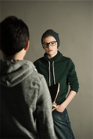 Boy with Skateboard talking to Teenage Boy, Studio Shot Stock Photo - Premium Royalty-Free, Code: 600-06752499