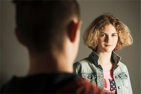 focus on background - Teenage Girl looking at Teenage Boy, Studio Shot Stock Photo - Premium Royalty-Free, Code: 600-06752493