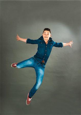 Portrait of Teenage Boy Jumping in Midair, Studio Shot Stock Photo - Premium Royalty-Free, Code: 600-06752506