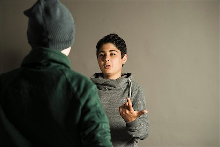 Teenage Boy Talking to another Boy, Studio Shot Stock Photo - Premium Royalty-Free, Code: 600-06752501