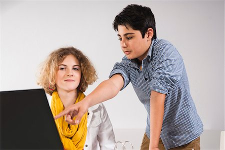 Teenagers looking at Laptop Computer, Studio Shot Stock Photo - Premium Royalty-Free, Code: 600-06752519