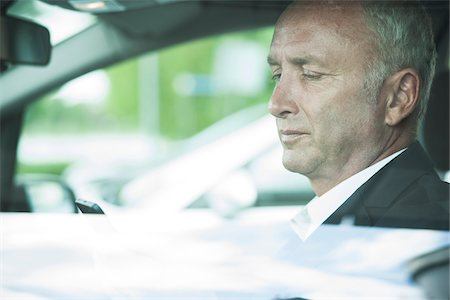 Businessman Looking at Cell Phone in Car, Mannheim, Baden-Wurttemberg, Germany Stock Photo - Premium Royalty-Free, Code: 600-06773354