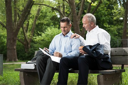 people sitting on bench - Businessmen Looking at Work on Park Bench, Mannheim, Baden-Wurttemberg, Germany Stock Photo - Premium Royalty-Free, Code: 600-06773351