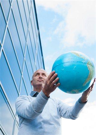 Businessman Holding Globe Outdoors, Mannheim, Baden-Wurttemberg, Germany Stock Photo - Premium Royalty-Free, Code: 600-06773368