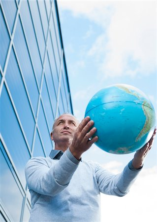 Businessman Holding Globe Outdoors, Mannheim, Baden-Wurttemberg, Germany Stock Photo - Premium Royalty-Free, Code: 600-06773368