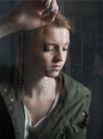 Portrait of teenage girl leaning against window, wet with raindrops Stock Photo - Premium Royalty-Free, Code: 600-06786756