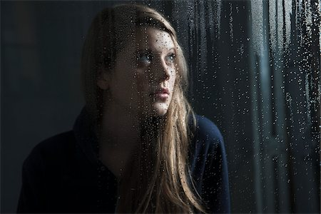 Portrait of young woman behind window, wet with raindrops, looking up Stock Photo - Premium Royalty-Free, Code: 600-06786759