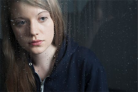 Portrait of young woman behind window, wet with raindrops, wearing hoodie Stock Photo - Premium Royalty-Free, Code: 600-06786765