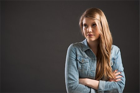 Portrait of young woman with long, blond hair, studio shot on grey background Stock Photo - Premium Royalty-Free, Code: 600-06786766