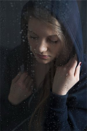 Portrait of young woman behind window, wet with raindrops, wearing hoodie, looking down Stock Photo - Premium Royalty-Free, Code: 600-06786760