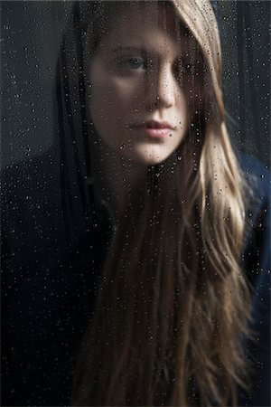 Portrait of young woman behind window, wet with raindrops, wearing hoodie Stock Photo - Premium Royalty-Free, Code: 600-06786761