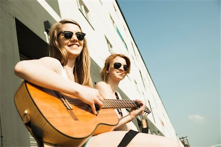 Young women sitting outdoors, hanging out and playing guitar, looking at camera, Mannheim, Germany Stock Photo - Premium Royalty-Free, Code: 600-06786779