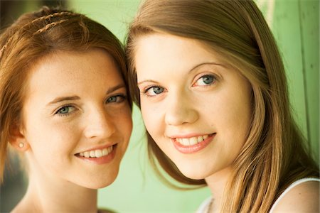 Close-up portrait of young women outdoors, smiling at camera Stock Photo - Premium Royalty-Free, Code: 600-06786772