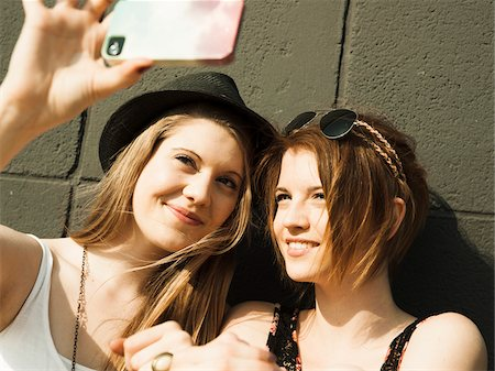 Close-up of young women taking photo of themselves with smart phone Stock Photo - Premium Royalty-Free, Code: 600-06786784