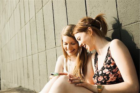 Young women sitting and leaning against wall, looking at smart phone together Stock Photo - Premium Royalty-Free, Code: 600-06786788