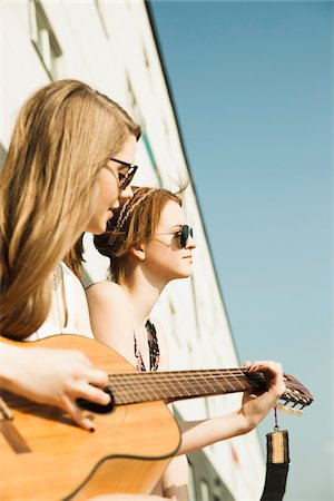 Young women sitting outdoors, hanging out and playing guitar, Mannheim, Germany Stock Photo - Premium Royalty-Free, Code: 600-06786781