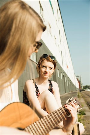 Young women sitting outdoors, hanging out and playing guitar, Mannheim, Germany Stock Photo - Premium Royalty-Free, Code: 600-06786782