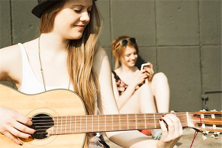 Young women sitting outdoors, hanging out and playing guitar, Mannheim, Germany Stock Photo - Premium Royalty-Free, Code: 600-06786783