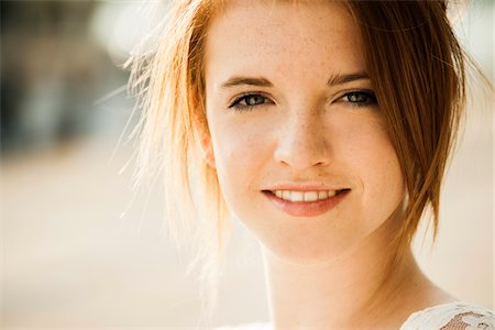 Close-up portrait of teenage girl outdoors, smiling at camera Stock Photo - Premium Royalty-Free, Code: 600-06786805