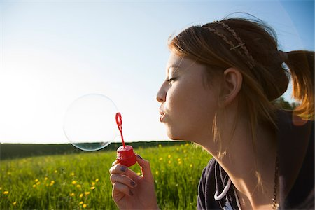 european (places and things) - Close-up of teenage girl blowing bubbles in field, Germany Stock Photo - Premium Royalty-Free, Code: 600-06786808