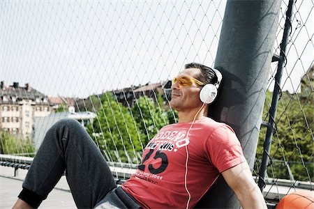 fit people - Mature man sitting on outdoor basketball court wearing headphones and listening to music, Germany Stock Photo - Premium Royalty-Free, Code: 600-06786834