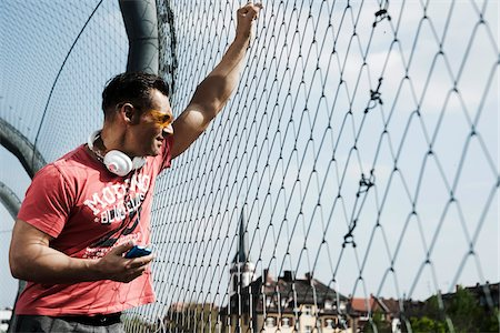 fit people - Mature man standing on outdoor basketball court holding MP3 player, Germany Stock Photo - Premium Royalty-Free, Code: 600-06786836