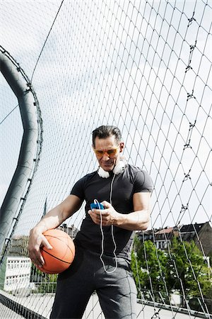 Mature man standing on outdoor basketball court holding basketball and looking at MP3 player, Germany Stock Photo - Premium Royalty-Free, Code: 600-06786837
