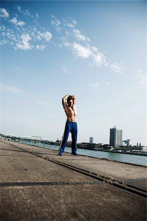 Mature man stretching on loading dock, Mannheim, Germany Stock Photo - Premium Royalty-Free, Code: 600-06786871