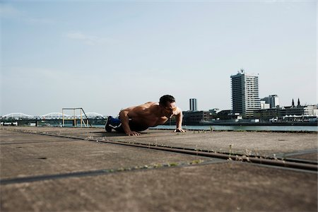 Mature man doing push-ups on loading dock, Mannheim, Germany Stock Photo - Premium Royalty-Free, Code: 600-06786873