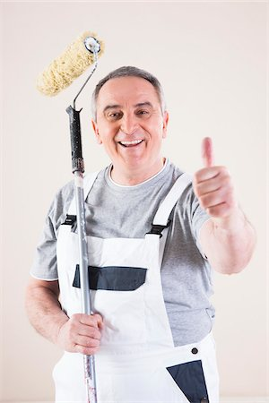 painter - Portrait of Painter giving Thumbs Up and holding Paint Roller, Studio Shot Stock Photo - Premium Royalty-Free, Code: 600-06786998