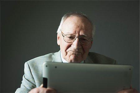 Elderly Man using Tablet Computer in Studio Stock Photo - Premium Royalty-Free, Code: 600-06787024