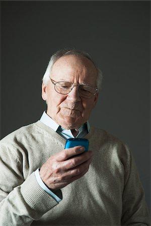 Elderly Man using Cell Phone in Studio Stock Photo - Premium Royalty-Free, Code: 600-06787025