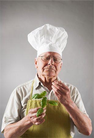 Elderly Man wearing Chef's Hat holding Basil Stock Photo - Premium Royalty-Free, Code: 600-06787027