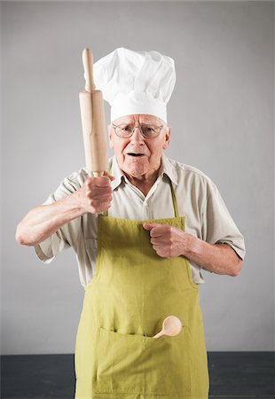 Elderly Man wearing Apron and Chef's Hat holding Rolling Pin in Studio Stock Photo - Premium Royalty-Free, Code: 600-06787028