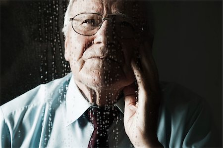 Elderly Man Looking out Window on Rainy Day Stock Photo - Premium Royalty-Free, Code: 600-06787029