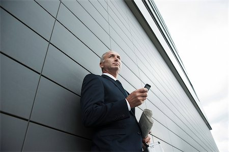 Portrait of businessman leaning against wall of building, holding cell phone, Mannheim, Germany Stock Photo - Premium Royalty-Free, Code: 600-06782185