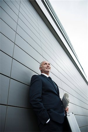Portrait of businessman leaning against wall of building, Mannheim, Germany Stock Photo - Premium Royalty-Free, Code: 600-06782186