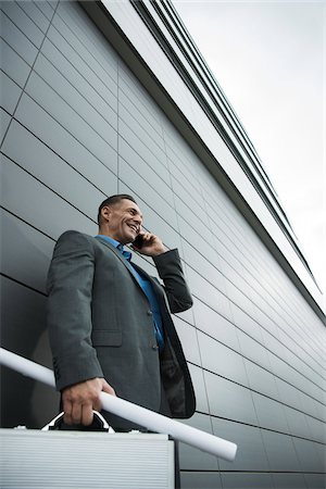 Businessman standing in front of wall of building using cell phone, Mannheim, Germany Stock Photo - Premium Royalty-Free, Code: 600-06782188