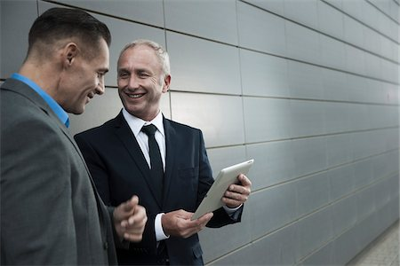 Mature businessmen standing in front of wall, talking and looking at tablet computer Stock Photo - Premium Royalty-Free, Code: 600-06782195